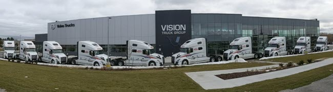 line of white trucks at vision truck group campus